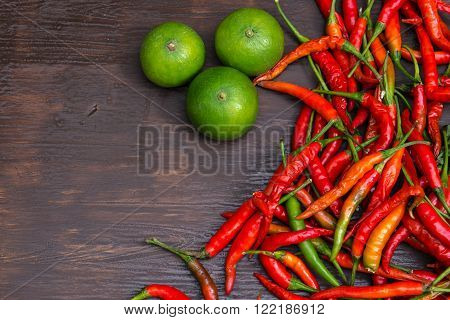 Chilli and lemons on wooden background, overhead view. low key tone.