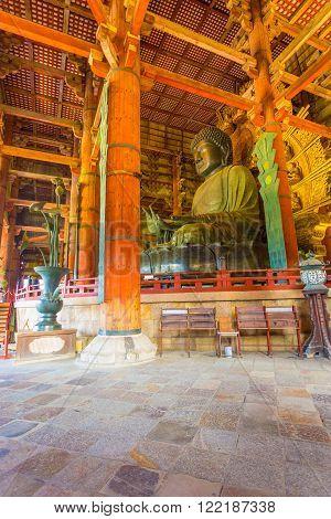 NARA, JAPAN - JUNE 25, 2015: Side profile of Daibutsu bronze Buddha and ceiling of inside the Great Buddha Hall Daibutsuden at Todai-ji temple in Nara Japan. Vertical interior