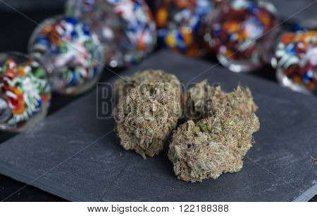 Granddaddy Purple medicinal medical marijuana buds on a slate surrounded by colorful glass.