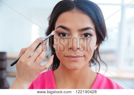 Hand of a makeup artist applying eyeshadow to pretty young model in beauty salon