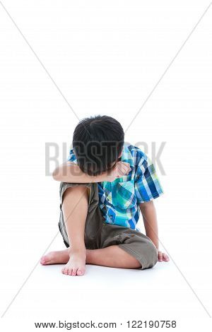 Little sad boy bare feet sitting on floor. Isolated on white background. Negative human emotions. Conceptual about children who lack warmth and affection, abandoned children. Free form copy space.