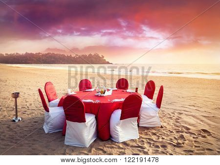 Beautiful romantic red wedding Table on tropical beach at purple sunset