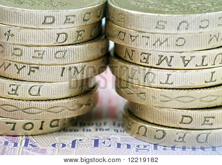 Close-up of stack of UK pound coins on bank note