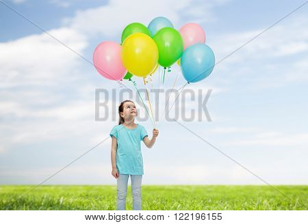 childhood, fashion, imagination and people concept - happy little girl looking up and holding bunch of colorful helium balloons on strand over blue sky and grass background