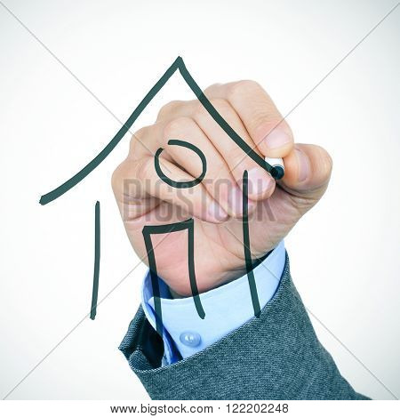 closeup of the hand of a young caucasian businessman in suit drawing a house with a pen in the foreground