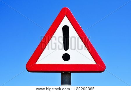 a triangular traffic sign with an exclamation mark against the blue sky