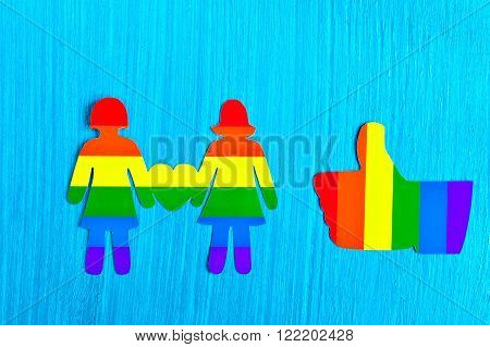 Two people from a paper heart in hands. Like gesture, thumbs up. Flag Colors of homosexuality. the relationship between the two women. Same-sex love. Homosexual relationships. Minorities. Logo LGBT.