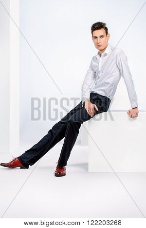 Full length portrait of a handsome young man in white shirt. Men's beauty, fashion. Studio shot. Isolated over white background.