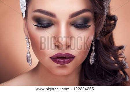 Beautiful bride in studio on brown background. Bridal make up