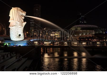 Singapore, Singapore - May 18, 2015: The Merlion statue and Esplanade Theatres in Singapore at night. The Merlion is a traditional creature in Singapore with a lions head and a body of fish.