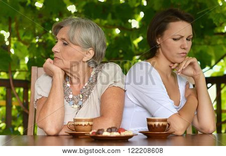 Senior mother and daughter sitting on the veranda and don't talk to each other.