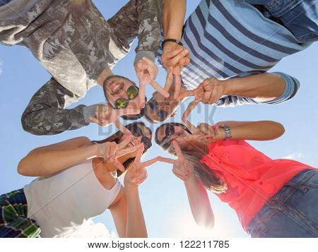 Friendship and teamwork concept. Group of friends looking down placed in a circle head to head at beautiful sunny day against clear blue sky.