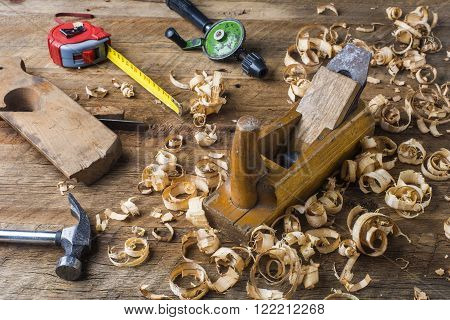 various carpentry tools and planer shavings on the workbench among