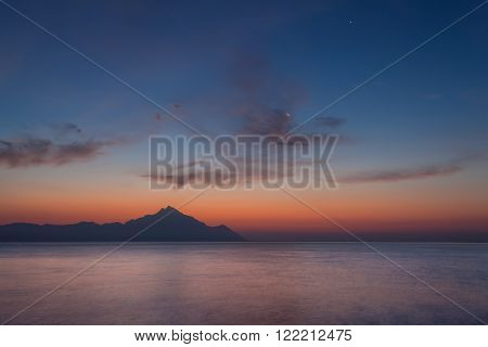 Beautiful dawn on Greek coast of Aegean sea with holy mountain Athos in background. Long exposure shot with motion blur effect. Chalkidiki, Greece.