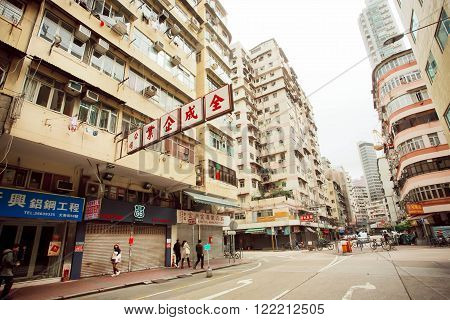 HONG KONG, CHINA - FEB 10: People walking on streets with tall concrete buildings in busy district of asian city on February 10, 2016. There are 1223 skyscrapers in Hong Kong.