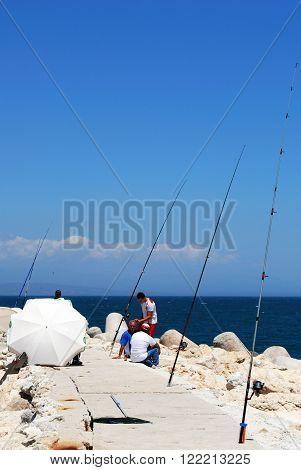 BENALMADENA, SPAIN - JUNE 2, 2008 - Fishermen sitting on the breakwater wall in the harbour Benalmadena Costa del Sol Malaga Province Andalusia Spain Western Europe, June 2, 2008.