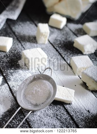 Homemade honey marshmallows on dark wood background