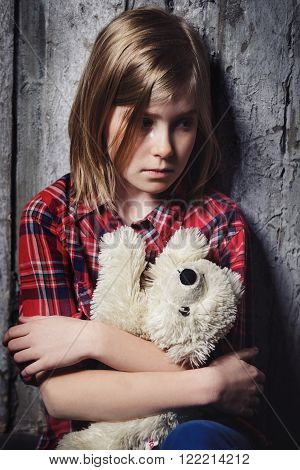 Depressed alone crying girl sitting with toy near wall