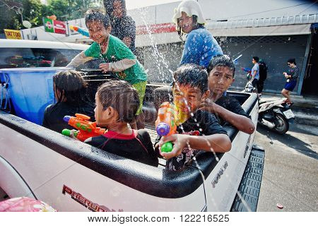 KO SAMUI, THAILAND - APRIL 13: Unidentified young thai small children in the trunk of a pickup in a water fight festival or Songkran Festival (Thai New Year) on April 13, 2014 in Chaweng Main Road, Ko Samui island, Thailand.