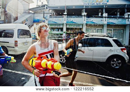KO SAMUI, THAILAND - APRIL 13: Unidentified man shooting water at other people in a water fight festival or Songkran Festival (Thai New Year) on April 13, 2014 in Chaweng Main Road, Ko Samui island, Thailand.