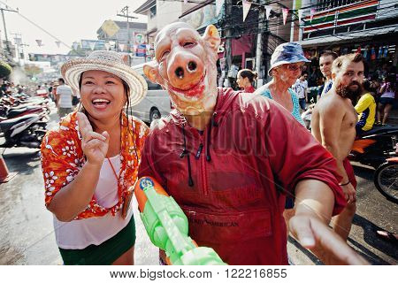 KO SAMUI, THAILAND - APRIL 13:  Unidentified thai girl and man with a pig mask posing on Songkran Festival (Thai New Year) on April 13, 2014 in Chaweng Main Road, Ko Samui island, Thailand.