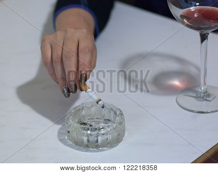 female hand with a cigarette over an ashtray near a glass of wine