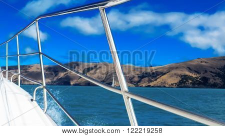 View of a boat with metal handrails and the sea with hills in the background