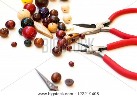 colorful wooden beads scissors and tools for creating fashion jewelry in the manufacturing process on a white table