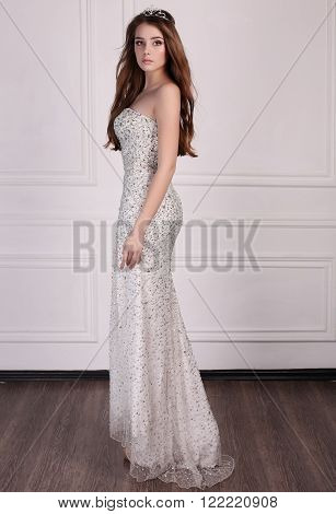 Beautiful Woman With Dark Hair Wears Elegant Dress And Precious Crown