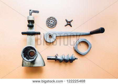 vintage meat grinder disassembled on the orange background