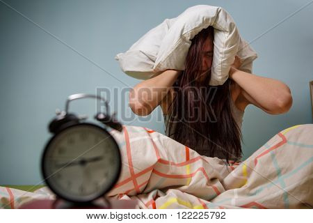Woman with a pillow over head.