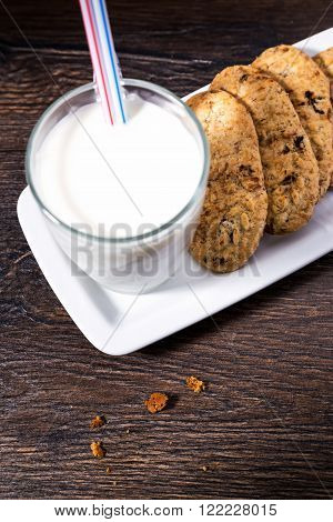 Chip cookies and glass of milk with drinking straws on old wooden background
