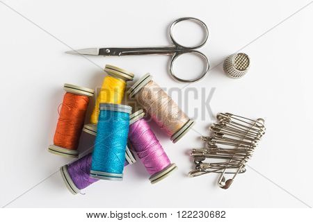 Sewing background. Accessories for needlework on wooden background. Spools of thread, scissors, sewing supplies. Set for needlework on white. Top view with copy space.