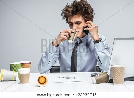 Coffee and conversation: While talking intensely on a phone, manager sitting with a cup. Modern office man at working place, sloth and laziness concept