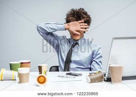 Upset businessman with eyes closed by hand is against xxx & porno online. Frustrated businessman close his eyes by hand turned away from the laptop screen