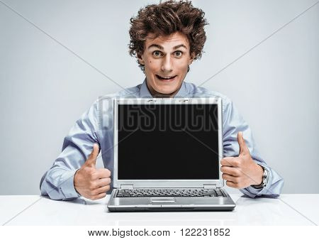 Happy salesman showing thumbs up success sign. Modern businessman at the workplace working with computer. Business concept