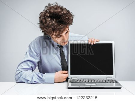 Cheerful manager looking at screen laptop. Modern businessman at the workplace working with computer. Business concept