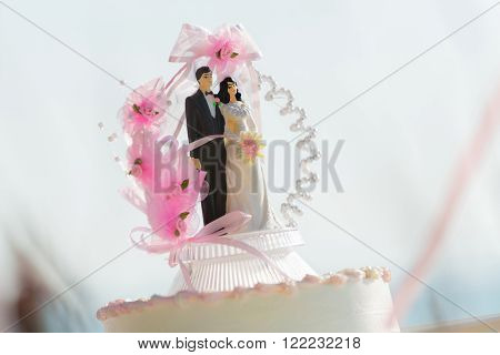 Doll weds of the bride and groom on a wedding cake that symbolizes the commitment to love one another.