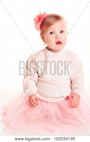 Funny baby girl 1-2 year old wearing stylish sweater and skirt over white. Looking at camera. Childhood.