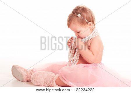 Baby girl 1-2 year old playing with pearl necklace over white. Sitting on floor in room. Childhood.