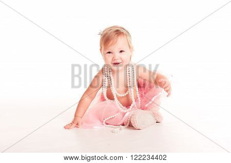 Smiling baby girl 1-2 year old having fun over white. Looking at camera. Wearing stylish skirt.