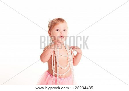 Smiling blonde girl 1-2 year old posing over white in room. Looking at camera.