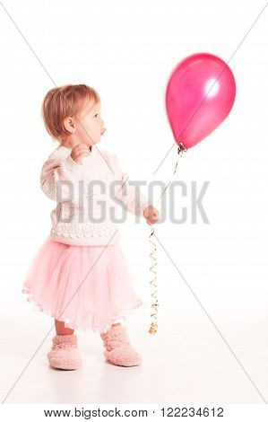 Funny baby girl 1-2 year old holding pink balloon over white. Isolated. Playful.