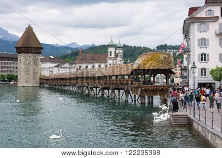Lucerne, Switzerland June 9 2013: Chapel Bridge and tower over the Reuss River with many tourists and swans.