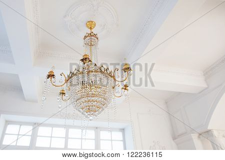 chandelier in the interior of white gold with glass pendants crystal