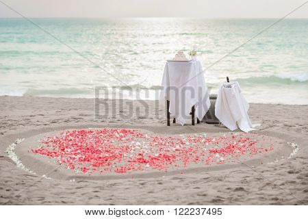 Table for the wedding ceremony, wedding cake, champagne and hearth shape of white and red petals on sand, sunset. Copy space.