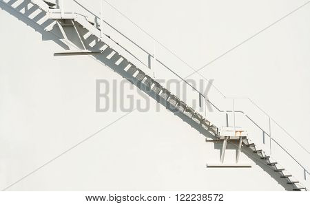 metallic staircase floating on an off-white wall background