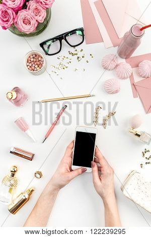 The female hands and smart phone against fashion woman objects on white. Concept of female mockup and comfortable  female workplace