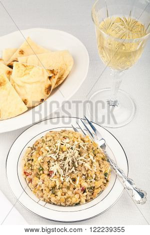 High-key image of white plate with quinoa lentil salad and bowl of naan bread.