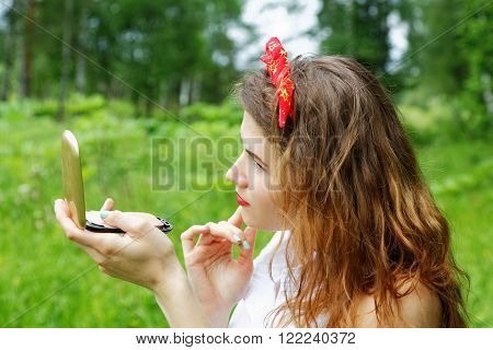 Girl With A Bow On Her Head Looking Into The Mirror On The Nature